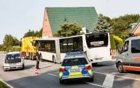 A policeman looks on as a bus, in which a passenger attacked fellow travellers with a knife in the afternoon, is towed away from the crime scene in the evening of July 20, 2018 in Kuecknitz near Luebeck in northern Germany. Picture: AFP.