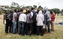 People gather during a meeting of over a hundred foreign nationals to discuss the way forward after they were left to fend for themselves, on 3 April 2019 at a park near the Musjid-us-Saliheen Mosque in Sherwood, Durban, after foreign nationals were displaced following xenophobic attacks. Picture: AFP