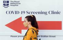 FILE: A woman queues outside a COVID-19 testing venue at The Royal Melbourne Hospital in Melbourne on 16 July 2020. Picture: AFP