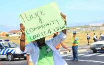 An activist carry a placard he protests against policing in Khayelitsha. Picture: Ndifuna Ukwazi Facebook page.