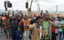 Alexandra township residents gesture and chant slogans as they clash with the Johannesburg Metro Police on 3 April 2019 in Johannesburg, South Africa during a total shutdown of the township due to a protest against the lack of service delivery. Picture: AFP