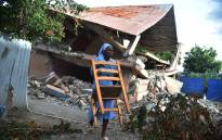 A nun carries a chair next to a school damaged by an earthquake that hit the north of Haiti on 6 October 6 in Gros Morne. Picture: AFP