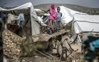 FILE: A girl and her brother stand on a donkey's cart next to their tent at a displacement camp for people affected by intense flooding in Beledweyne, Somalia, on 14 December 2019. Picture: AFP