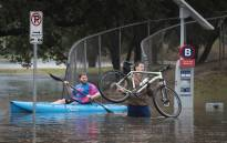 Residents navigate a flooded street that has been inundated with water from Hurricane Harvey on 27 August 2017 in Houston, Texas. Picture: AFP