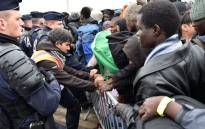 """French riot police hold back migrants as they clear the """"Jungle"""" migrant camp in Calais. Picture: AFP"""