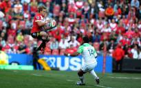 Lions' Andries Coetzee (L) jumps with the ball past Highlanders' Waisake Naholo during the Super XV rugby semi-final match between Lions and Highlanders at Ellis Park on July 30, 2016 in Johannesburg, South Africa. Picture: AFP.""