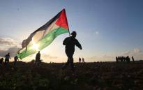 FILE: A Palestinian protester carries a national flag during a demonstration near the border between Israel and Khan Yunis in the southern Gaza Strip, on 21 December 2018. A 16-year-old Palestinian was killed today by Israeli fire during border protests and clashes east of Gaza City, the health ministry in the Hamas-run enclave said. Picture: AFP.