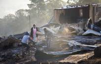 FILE: Children play in the debris of 40 shacks that burnt down in White Location, an informal settlement in Knysna. Picture: Thomas Holder/EWN.