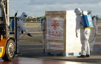 This handout photo taken on February 28, 2021 and received from the Presidential Communications Operations Office (PCOO) shows workers in protective suits disinfecting one of the crates containing the first batch of Sinovac vaccines shortly after its arrival onboard a Chinese air force plane at Villamor air base in Manila. Picture: Presidential Communications Operations Office / AFP