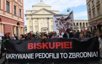 """FILE: Protesters hold a banner reading """"Bishop, Hiding Pedophilia is a Crime"""" and a map reading """"Map of Church Pedophilia in Poland"""" with 255 documented cases of sexual abuse of minors by the country's Catholic priests, during a protest against alleged child sex abuse in the Catholic church in Warsaw on 7 October 2018, demanding the church to  stop protecting paedophile priests. Picture: Janek SKARZYNSKI/AFP"""