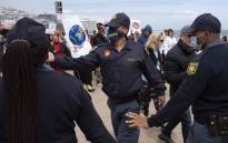 Members of the South African Police Services intervene during a demonstration against the vaccination certificate and the requirement to wear masks amid the COVID pandemic on Seapoint Promenade in Cape Town, on 2 October 2021. More than 1.000 people took part in the protest. Picture: RODGER BOSCH/AFP