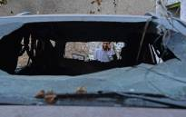 A relative of Ezmarai Ahmadi, is pictured through the wreckage of a vehicle that was damaged in a US drone strike in the Kwaja Burga neighbourhood of Kabul on September 18, 2021. Ezmarai Ahmadi was wrongly identified as an Islamic State militant by US intelligence, who tracked his white Toyota for eight hours on August 29 before targeting the car, killing seven children and three adults. Picture: Hoshang Hashimi / AFP