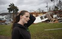 FILE: Haley Nelson stands in front of what is left of one of her father's trailer homes after hurricane Michael passed through the area on 10 October 2018 in Panama City, Florida. Picture: AFP.