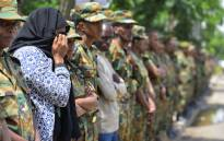 A woman mourns among soldiers standing guard ahead of the National funeral service, at the millennium hole in Addis Ababa, of Chief of Staff of the Ethiopian defence forces Seare Mekonnen and of Major-General Geza'e Abera, a retired former senior official in the Ethiopian army on 25 June 2019. Picture: AFP