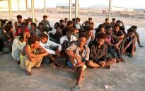 Rescued migrants sit on the coast of Khoms, some 100 kilometres (60 miles) from the Libyan capital Tripoli, on 26 July 2019. Picture: AFP