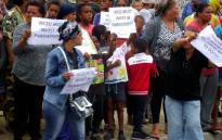 A group of Parkwood residents holding placards outside Parkwood Primary school during a demonstration against what they call falling apart school buildings. Picture: Supplied.