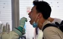 A swab sample is taken from a man to be tested for the COVID-19 coronavirus at a hospital in Beijing on 2 August 2021, amid the country's most widespread coronavirus outbreak in months. Picture: Noel Celis/AFP