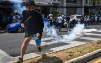 Protesters run after police fired tear gas to disperse them during a demonstration against the military coup in Yangon on 28 February 2021. Picture: AFP