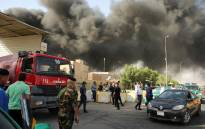 Members of the fire brigade and the Iraqi federal police stand outside the country's biggest ballot warehouse, where votes for the eastern Baghdad district were stored, as a column of black smoke billows from a the building, in the capital Baghdad on 10 June, 2018. Picture: AFP