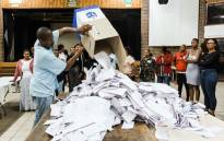 FILE: An Independent Electoral Officer (IEC) opens a ballot box as counting begins at the Addington Primary School after voting ended at the sixth national general elections in Durban, on 8 May 2019. Picture: AFP