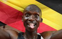 Uganda's Joshua Cheptegei waves an Uganda national flag as he celebrates after winning and breaking the world record in the men's 5000 metre event during the Diamond League Athletics Meeting at The Louis II Stadium in Monaco on 14 August 2020. Picture: AFP / POOL.
