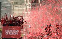 Liverpool's German manager Jurgen Klopp (C) holds the European Champion Clubs' Cup trophy as he stands with his players during an open-top bus parade around Liverpool, north-west England on 2 June 2019. Picture: AFP