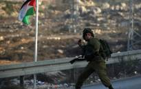 FILE: An Israeli soldier hurls a smoke grenade during clashes with Palestinian youth close to the Jewish settlement of Bet El, in the West Bank city of Ramallah. Picture: AFP.