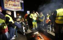 """Yellow vest protesters listen near a loudspeaker and a banner reading """"everybody together"""" on A9 road near Le Boulou, southern France on 10 December, 2018 as French president delivers a TV speech following the so-called """"yellow jacket crisis"""". Picture: AFP"""