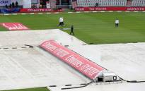 Umpires inspect the rain-soaked pitch as rain delays the start of play on the fourth day of the third Test cricket match between England and the West Indies at Old Trafford in Manchester, northwest England on 27 July 2020. Picture: AFP