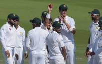 Pakistani spinner Yasir Shah (C) holds the ball as he celebrates with teammates after breaking fastest 200 wickets record during the fourth day of the third and final Test cricket match between Pakistan and New Zealand at the Sheikh Zayed International Cricket Stadium in Abu Dhabi on 6 December, 2018. Picture: AFP