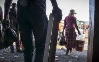 FILE: Burundi national Harayandi Moustapha (left) watches as looters carry out what is left of his spaza shop and its contents. It was first looted and burnt the night before. Picture: Thomas Holder/EWN.