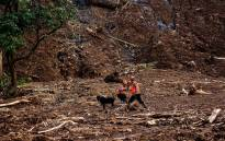 This picture taken on 27 January 2019 shows an Indonesian rescuer using a sniffer dog to search for survivors after a landslide in Gowa in South Sulawesi. Picture: AFP