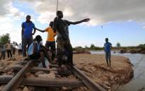 Boys fish from a railway track which was swept away by flash floods from the Ntamoyo River in Bangula on 23 January, 2015. Picture: Aletta Gardner/EWN.