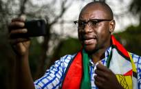 This file photo taken on 19 May 2016 shows Zimbabwean cleric Evan Mawarire, wrapped in the Zimbabwean national flag, recording an instalment of his #ThisFlag video series. Picture: AFP.