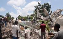 People search through the rubble of what used to be the Manguier Hotel after the earthquake hit on 14 August 2021 in Les Cayes, southwest Haiti. Picture: Stanley Louis/AFP