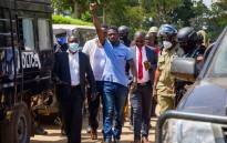 Ugandan musician turned politician Robert Kyagulanyi (C), also known as Bobi Wine, raises his arm as he walks to the court in Inganga, on November 19, 2020. Picture: AFP.