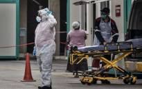 Emergency paramedics wearing a full COVID-19 coronavirus personal protective equipment (PPE) transfer an empty gurney to an ambulance at the Greenacres Hospital in Port Elizabeth, on 10 July 2020. Picture: AFP