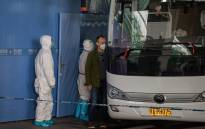 A member of the World Health Organization (WHO) team investigating the origins of the COVID-19 pandemic boards a bus following their arrival at a cordoned-off section in the international arrivals area at the airport in Wuhan on 14 January 2021. Picture: NICOLAS ASFOURI/AFP