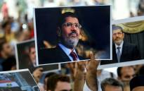 People hold picture of Egyptian President Mohamed Morsi during a symbolic funeral cerenomy on 18 June 2019 at Fatih mosque in Istanbul. Picture: AFP