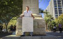 Johan Willemse of the Red October movement stands chained to the statue of Jan van Riebeeck in Cape Town to protest the vandalism of monuments across the country on 8 April 2015. Picture: Aletta Gardner/EWN