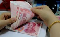 FILE: A teller counts yuan banknotes in a bank in Lianyungang, east Chinas Jiangsu province. Picture: AFP.