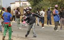 FILE: Protesters hurl stones in Harare on 4 July, 2016 during clashes with Zimbabwe's riot police. Picture: AFP.