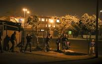 """A Saps tactical team makes a late night sweep as a Manenberg residents walks across a """"no-man's-land"""" after about 30 shots were fired in the space of an hour. Picture: Thomas Holder/EWN"""