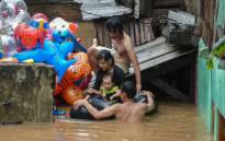 A family evacuates their home by using an inflated inner-tube after rain all night caused local flooding in Jakarta on 1 January 2020. Picture: AFP