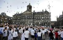 People release white balloons in the air during a silent march in memory of the victims of the downed Malaysia Airlines flight MH17, on 23 July 2014. Picture: AFP.