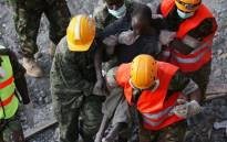Rescue workers carry a survivor from the rubble of an apartment block, which collapsed six days previously, on 5 May 2016 in Nairobi. Picture: AFP.