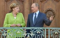 German Chancellor Angela Merkel and Russian President Vladimir Putin chat as they pose for the media on 18 August 2018 at Schloss Meseberg castle in Meseberg, northeastern Germany, where they meet to discuss conflicts in Syria and Ukraine as well as energy issues. Picture: AFP.