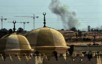 FILE: Smoke rises behind a mosque as NATO planes bombard Moamer Kadhafi troops positions close to the eastern gate of the city of Sirte, Kadhafi's home town on 25 September, 2011. Picture: AFP