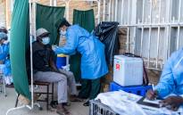 A member of the military administers the SinoVac vaccine to a citizen at a mobile clinic in Emganwini township, Bulawayo, Zimbabwe, on 3 August 2021. Picture: Zinyange Auntony/AFP