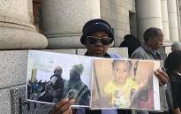 Lumka Makasi's grandmother, Nobantu Bakana, holds up pictures of the toddler who was murdered by her mother's husband. Picture: Lauren Isaacs/EWN.